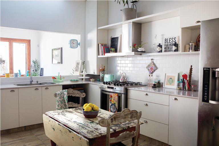 Los electrodomésticos de color (SMEG) se recortan en la caja blanca de la cocina. Junto a la pileta, barco portacubiertos (Gato Store)