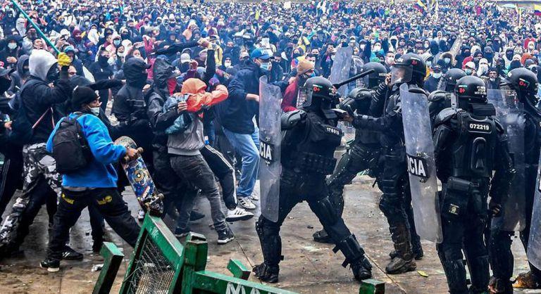 Manifestantes chocan con la policía antidisturbios durante una protesta contra un proyecto de reforma tributaria lanzado por el presidente colombiano Iván Duque, en Bogotá, Colombia (AFP/ Juan Barreto)