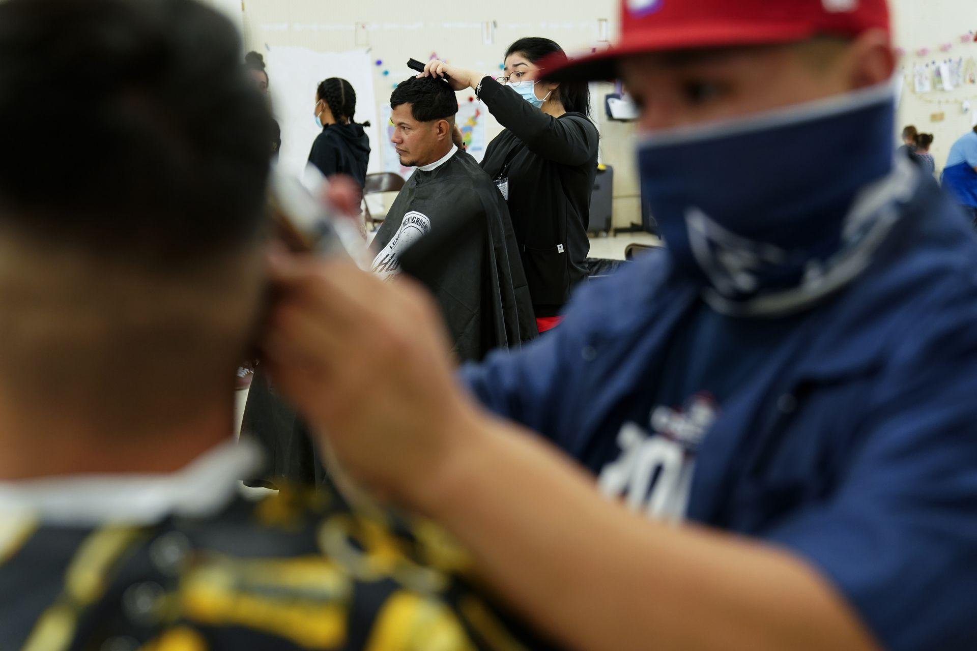 Inmigrantes cortan el pelo en un refugio ubicado en McAllen, en Texas