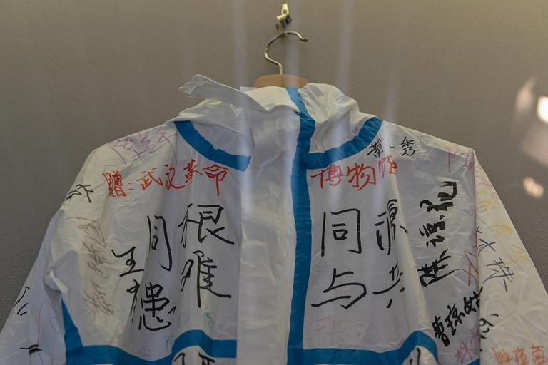 Esta foto tomada el 5 de agosto de 2020 muestra un traje firmado y donado por un equipo médico de Hainan que apoyó a la provincia de Hubei durante el cierre local de Covid-19, exhibido en una sala de la exposición del Museo de la Revolución de Wuhan