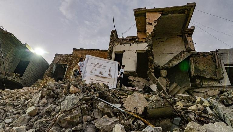 Chicos despliegan un poster de Francisco sobre los escombros de una casa destruida al lado de las ruinas de una iglesia cristiana de Mosul