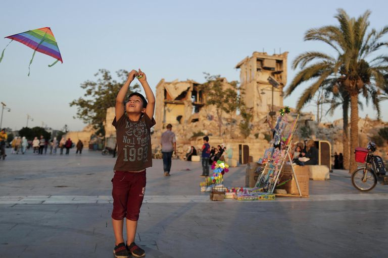 Un chico juega con un barrilete frente a la Ciudadela Medieval de Aleppo