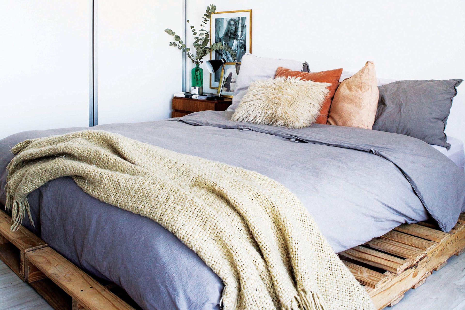 Funda de edredón y almohadones (todo de Philomena Home), manta tejida (Arredo) y mesa de luz (Mercado Libre).