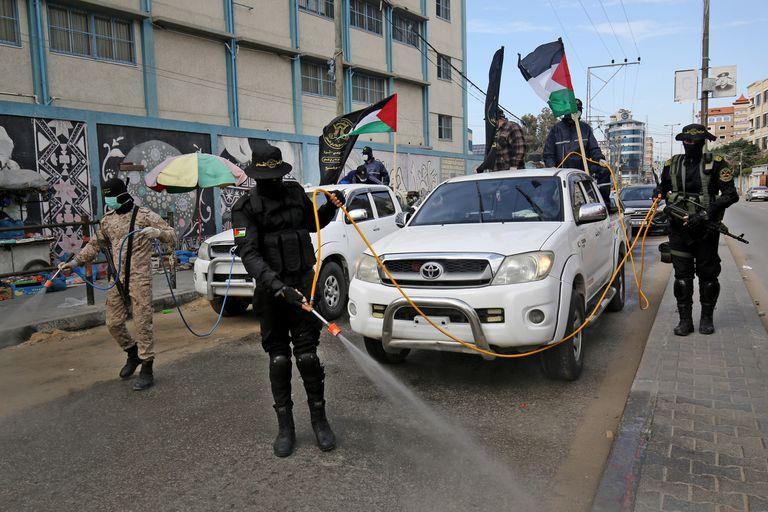 Miembros del ala armada de la Jihad Islámica palestina, las Brigadas Al-Quds, rocían desinfectante en las calles de Rafah, en el sur de la Franja de Gaza como parte de la campaña contra el coronavirus