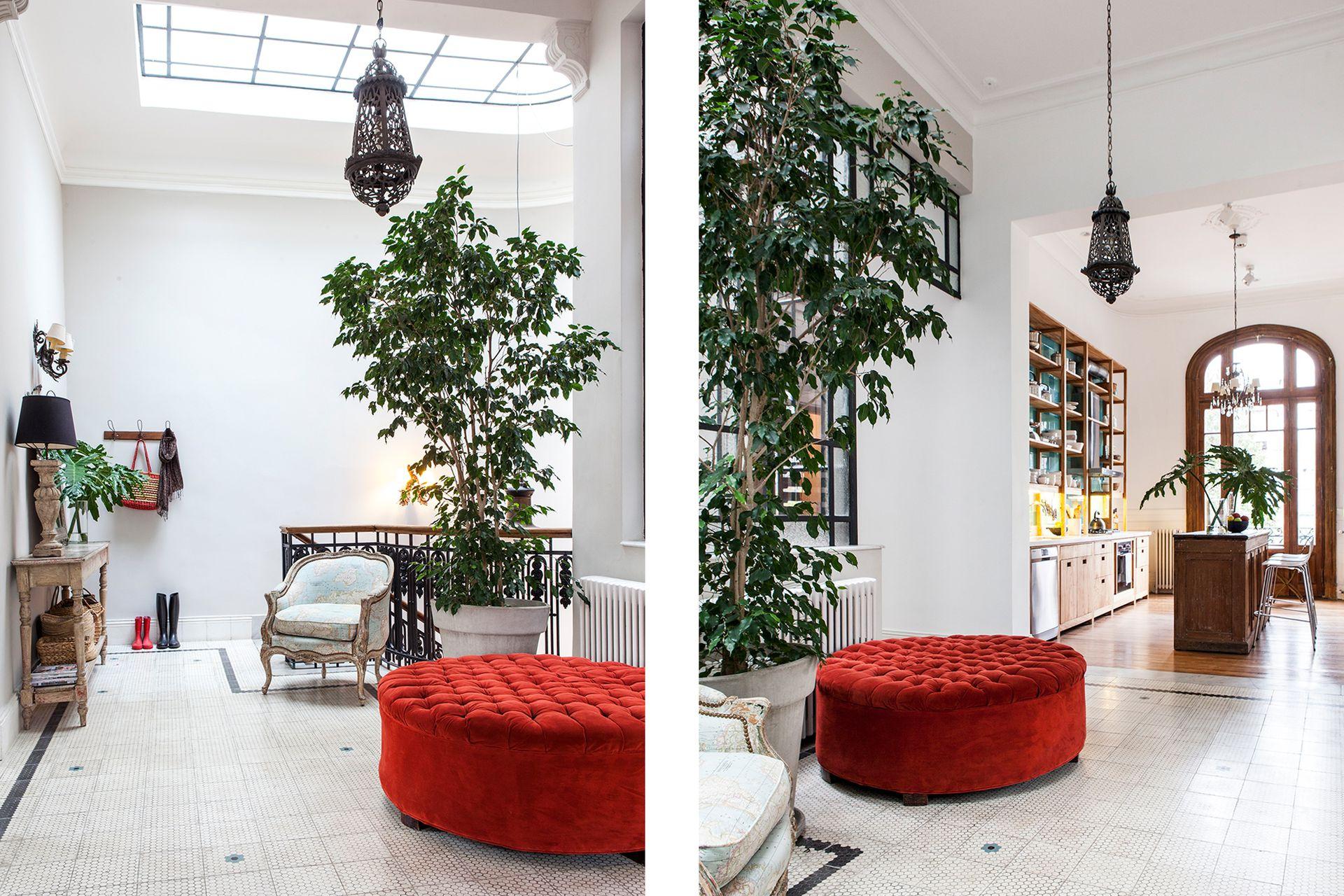 Una lámpara marroquí de hierro (similares en Desde Asia), un sillón vintage y un puf tapizado en pana color tomate (De Levie) ambientan el espacio que antecede a la cocina.