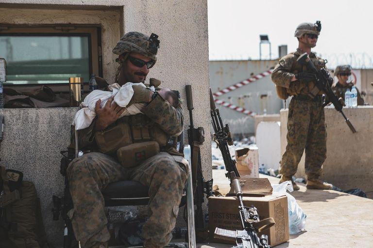 Un marine con un niño en el aeropuerto de Kabul. Photo: Isaiah Campbell/U.S. Marine Corps via ZUMA Wire/dpa
