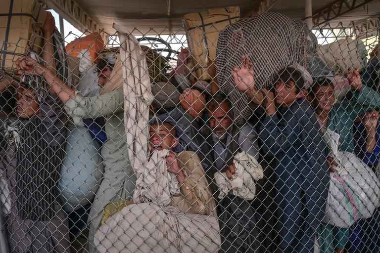 Adultos con niños se apresura a cruzar la puerta fronteriza a Pakistán desde la frontera con Afganistán en Spin Boldak el 25 de septiembre de 2021
