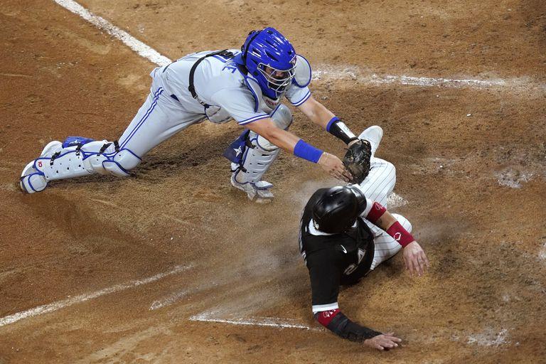 El catcher de los Azulejos de Toronto Reese McGuire elimina a Yasmani Grandal, de los Medias Blancas de Chicago, en el plato en el cuarto inning del juego de la MLB que enfrentó a ambos equipos, el 9 de junio de 2021, en Chicago. (AP Foto/Charles Rex Arbogast)