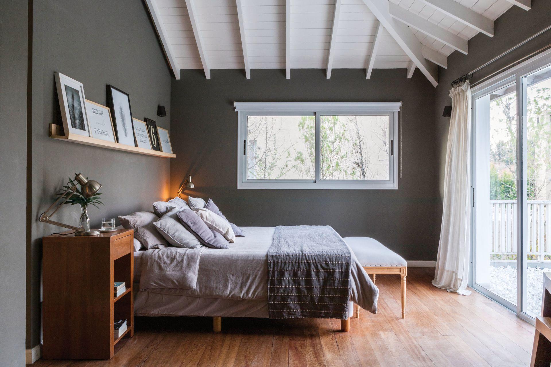 En el dormitorio con salida a una terraza propia y con escritorio integrado, somier (La Cardeuse), mesas de noche (Laura O), banco al pie de la cama (Paul French Gallery) y cuadros (Organizza).