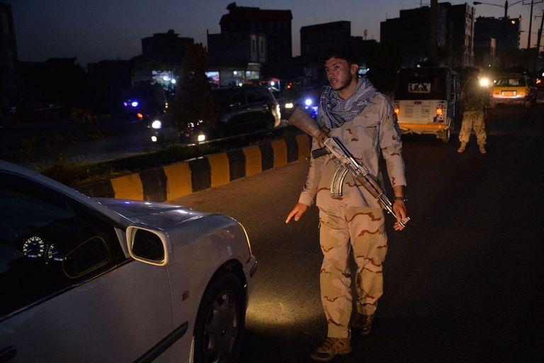 Un personal de seguridad detiene un vehículo en un punto de control en Herat, cuando se impuso un toque de queda nocturno