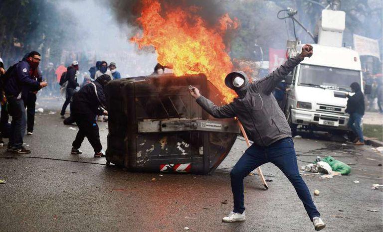 Un manifestante lanza piedras a la policía en la Plaza del Congreso, mientras sesionaban los diputados