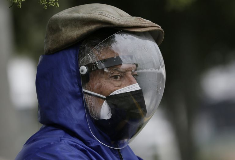 Un hombre vestido con un protector facial completo y una máscara doble para evitar el contagio de COVID-19 espera su turno para ser vacunado en Quito, Ecuador, el jueves 6 de mayo de 2021. (AP Foto/Dolores Ochoa)
