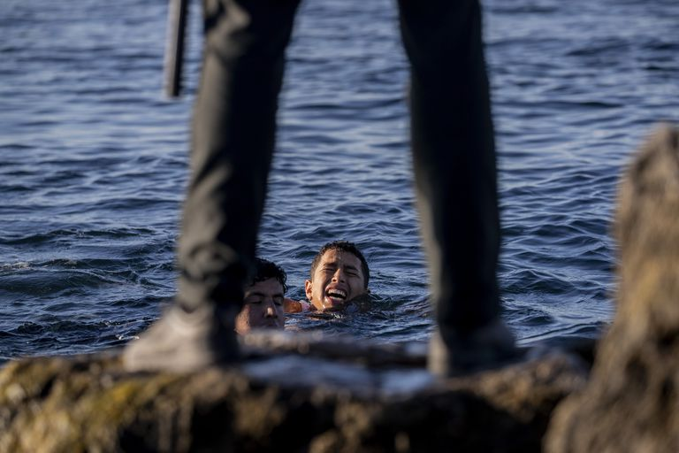 Un guardia civil español espera a que unos jóvenes migrantes que nadaron desde Marruecos a Ceuta lleguen a la orilla