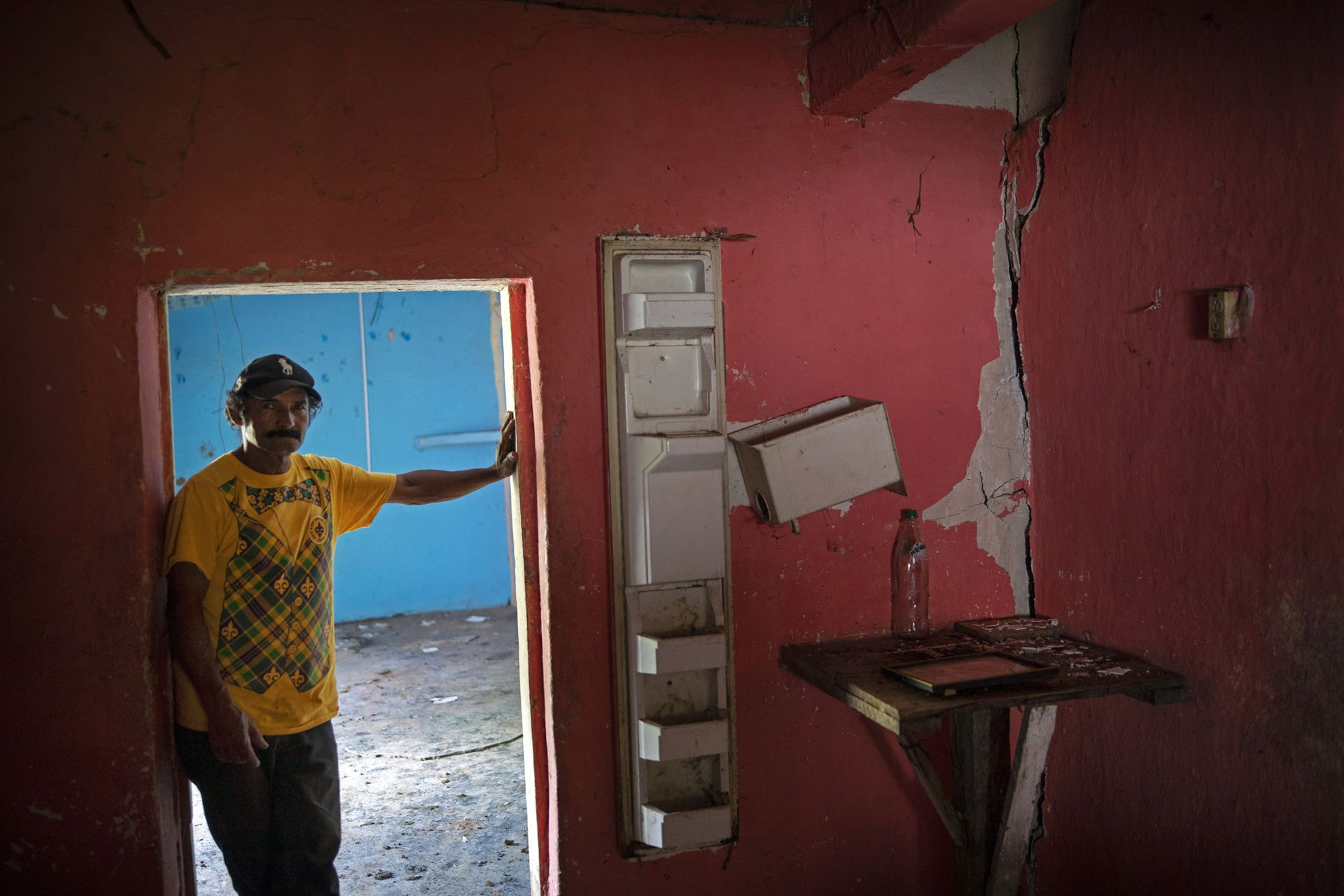 """Orlando Perdomo, de 56 años, en su casa dañada por un deslizamiento de tierra provocado por los huracanes Eta e Iota, en el pueblo de La Reina, Honduras. """"Cuando se abrieron las primeras grietas en la tierra después del Huracán Mitch en 1998, mi padre dijo que no viviría para verlo, pero que veríamos desaparecer el pueblo, y que el futuro traería la muerte"""", recuerda Perdomo"""