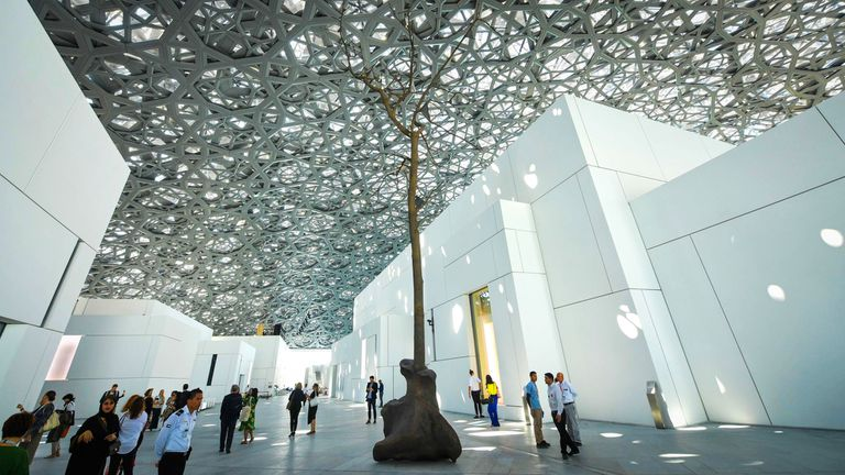 La gente camina cerca de una escultura del artista italiano Giuseppe Penone en el Museo Louvre Abu Dhabi