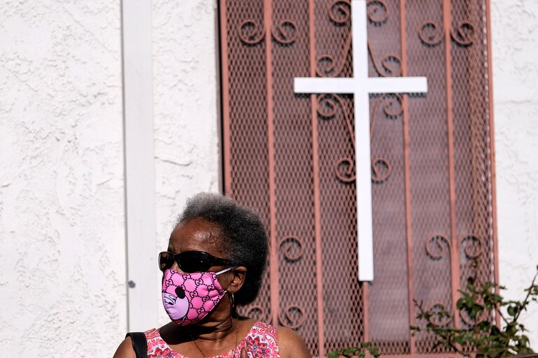 Una mujer con una mascarilla espera en la fila en la Iglesia de Cristo de Southside en Los Ángeles, California, el 18 de enero de 2021 mientras se administran pruebas de PCR y de anticuerpos a los residentes locales en honor al Día de Martin Luther King Jr
