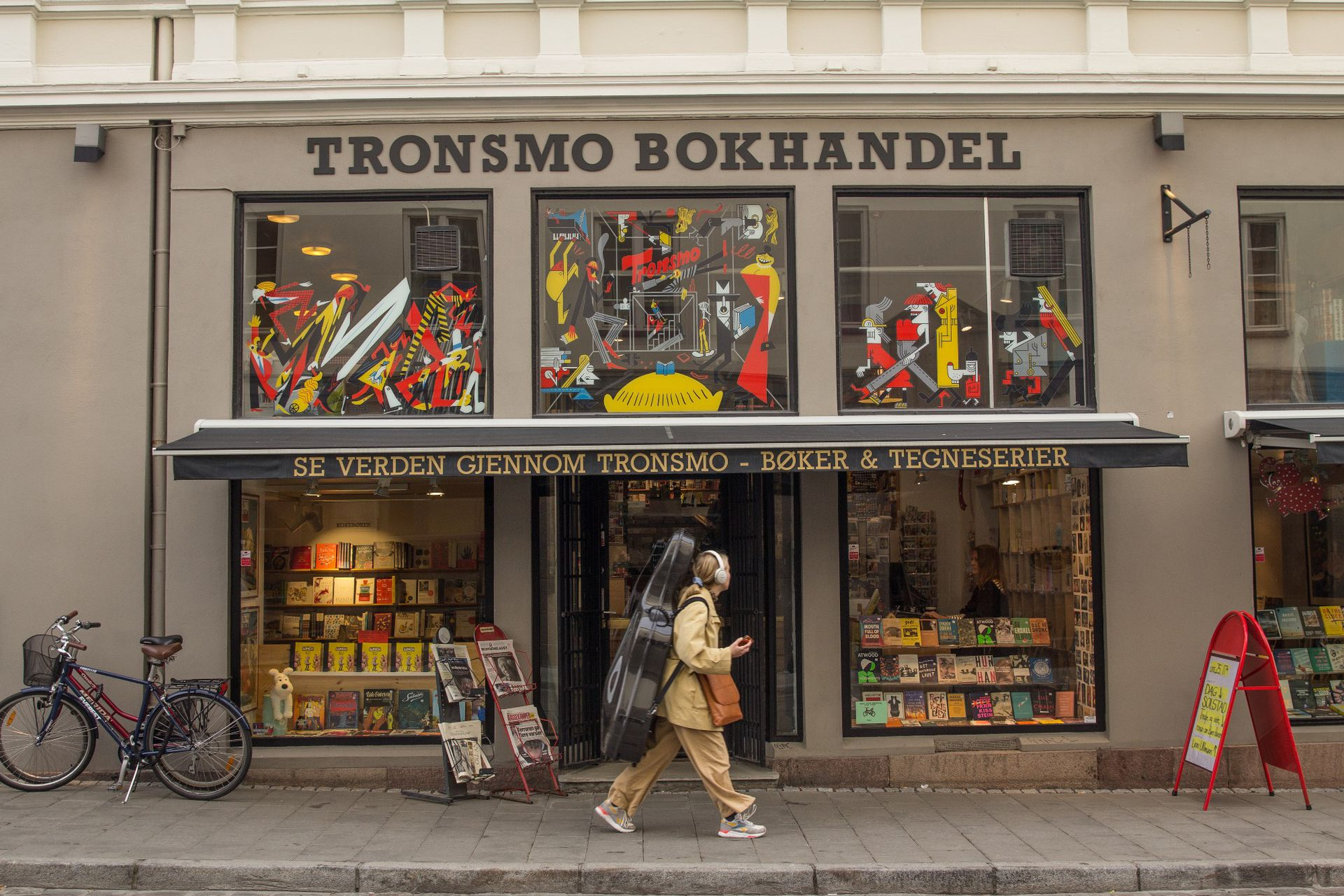 Una violonchelista pasa junto a Tronsmo, la librería independiente más antigua de la ciudad con una gran selección de cómics y libros en otros idiomas.
