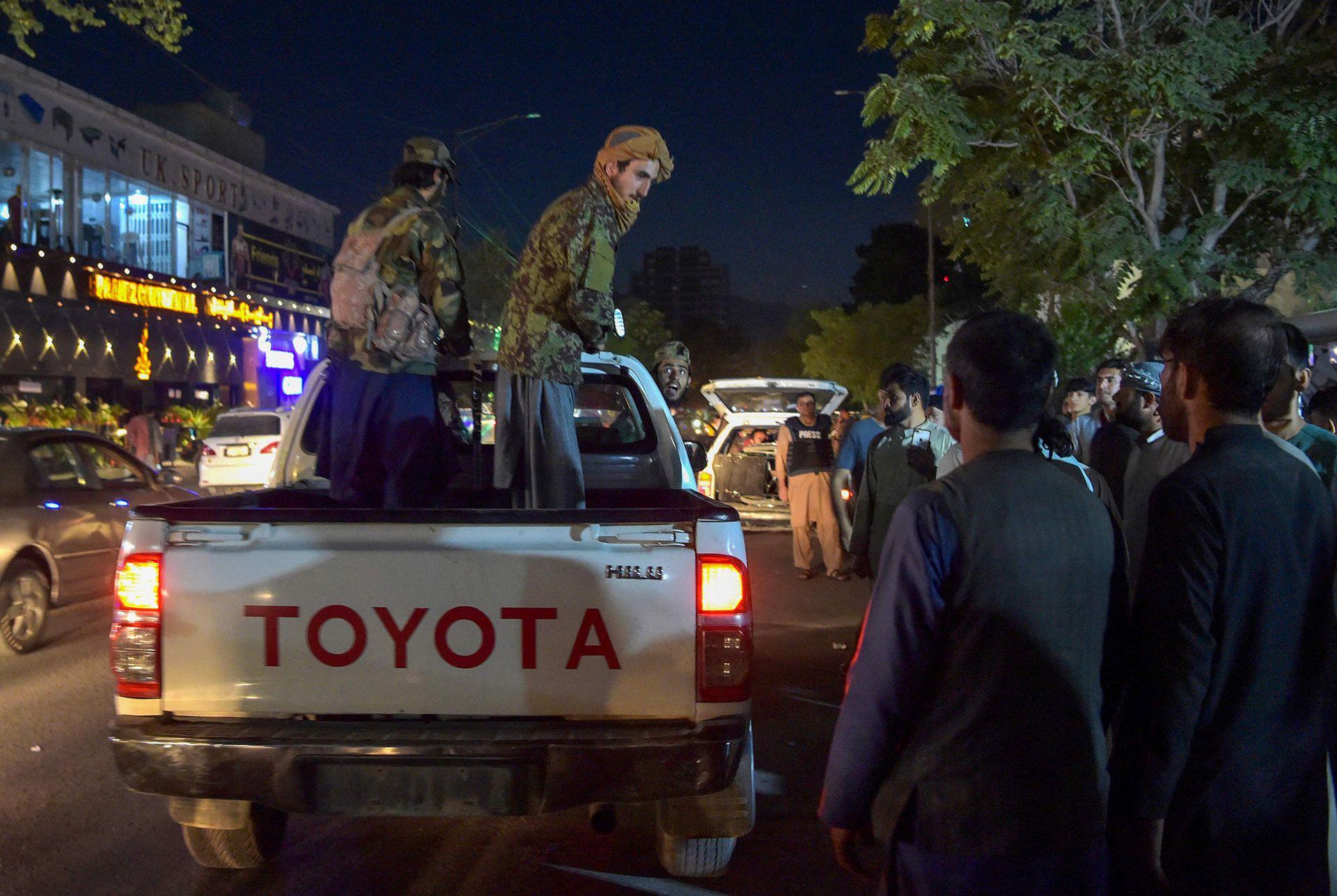Combatientes talibanes se trasladan en una camioneta mientras los voluntarios traen a los heridos para recibir tratamiento después de poderosas explosiones, que mataron al menos a una decena de personas, fuera del aeropuerto de Kabul