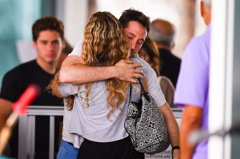Las personas se abrazan mientras esperan noticias sobre familiares en el Centro Comunitario en Surfside al norte de Miami Beach, Florida