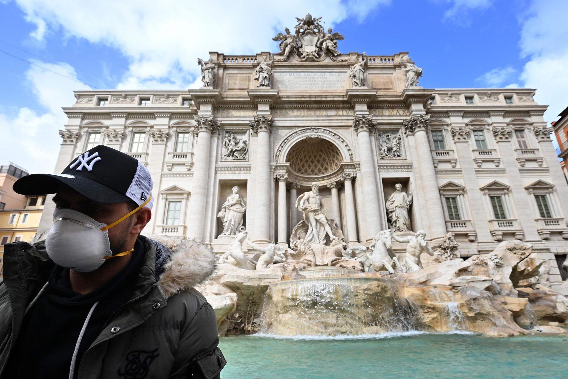 Un turista usa un barbijo frente a la Fontana de Trevi en el centro de Roma, el 3 de marzo de 2020. En Roma, lejos de los puntos críticos del norte, más del 50 por ciento de las reservas se cancelaron hasta finales de marzo, dijo la asociación de hoteles Federalberghi.