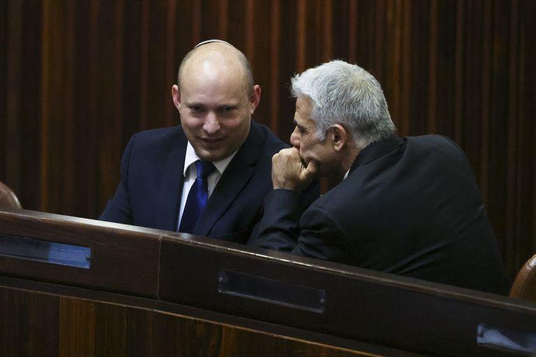 El líder del partido Yamina, Naftali Bennett (izquierda), sonríe mientras habla con el de Yesh Atid, Yair Lapid, durante una sesión extraordinaria en el Knesset, el parlamento israelí, en Jerusalén, el 2 de junio de 2021