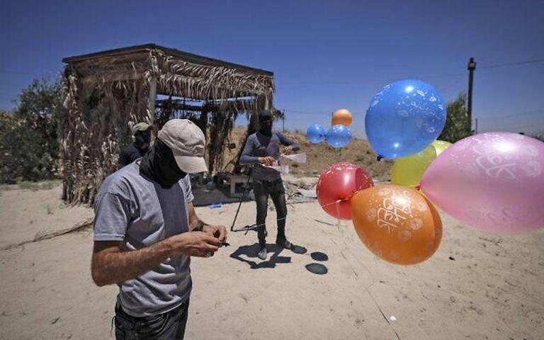 Terroristas enmascarados de la Jihad Islámica Palestina preparan globos incendiarios al este de la ciudad de Gaza, para lanzarlos a través de la valla fronteriza hacia Israel el 15 de junio de 2021