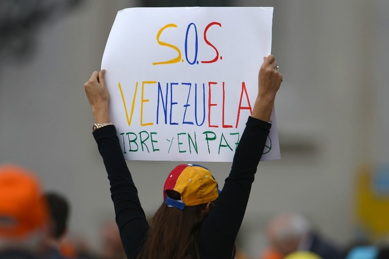 Una opositora a Nicolás Maduro pide con un cartel ayuda con la leyenda S.O.S. Venezuela