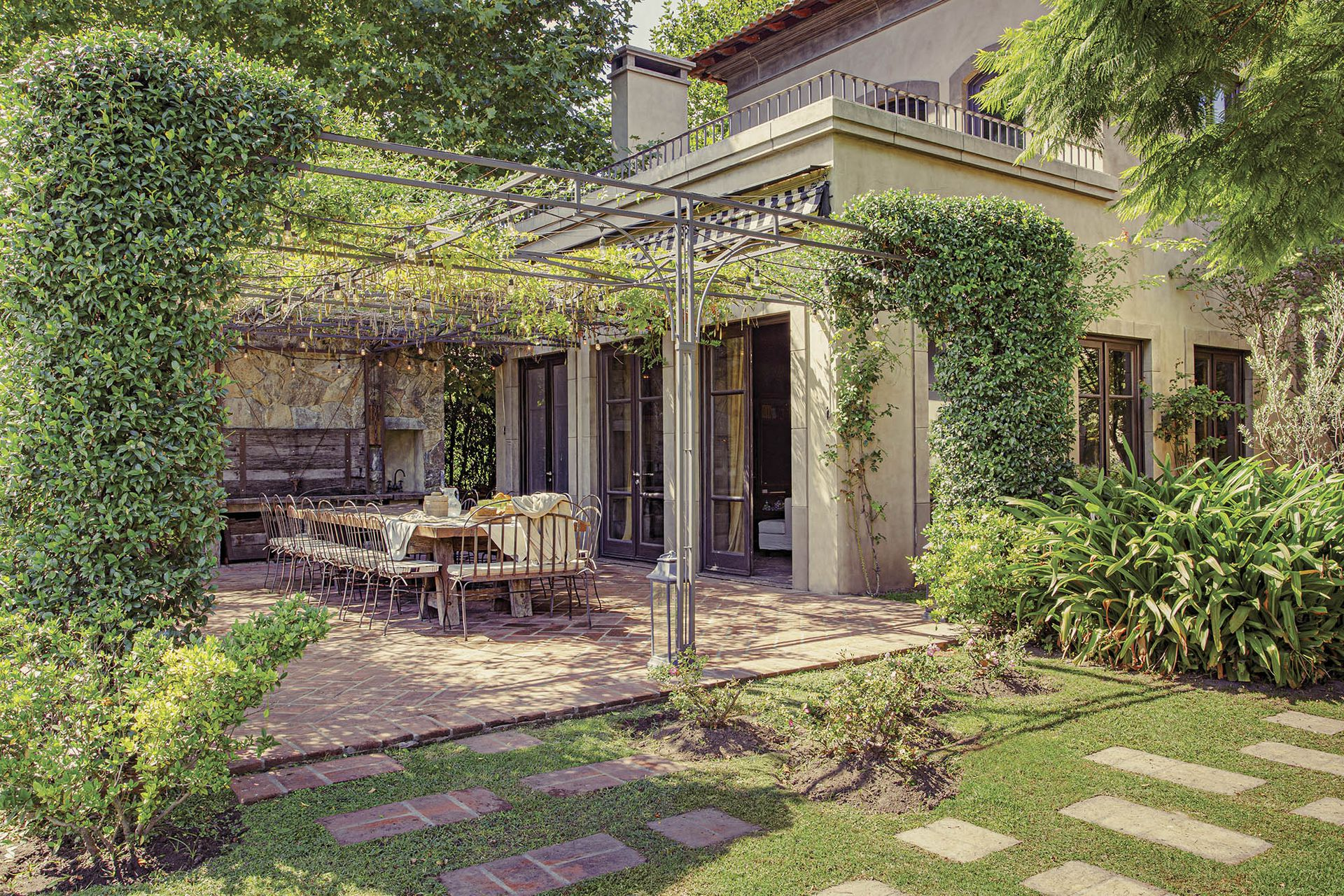 Bajo la pérgola de hierro se ubicó la mesa con tapa de durmientes de pino tea (Amighini). Sillas y sillones de hierro (Bielfer). Los pisos son de ladrillones de Córdoba.