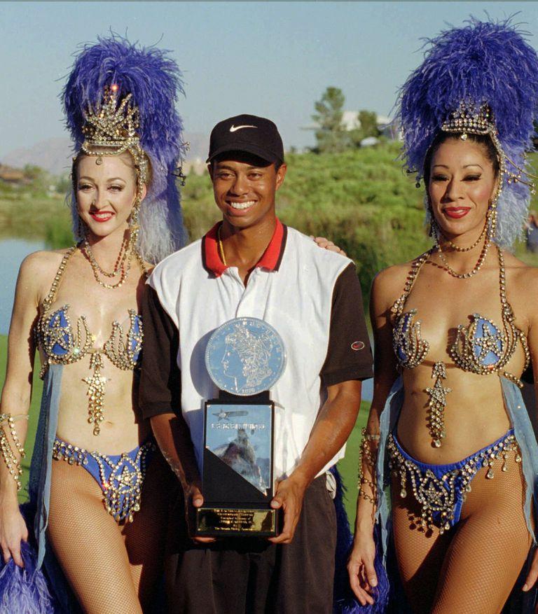 ARCHIVO - En esta foto de archivo del 6 de octubre de 1996, Tiger Woods, en el centro, posa con las bailarinas de Jubilee de Ballys, Windi See, a la izquierda, y Gracie Martínez después de ganar su primer torneo de golf profesional en el Las Vegas Invitational en Las Vegas. Hace veinticinco años esta semana, Woods ganó por primera vez en el PGA Tour en el Las Vegas Invitational, cambiando el golf para siempre. (Foto AP / Lennox McLendon, archivo)
