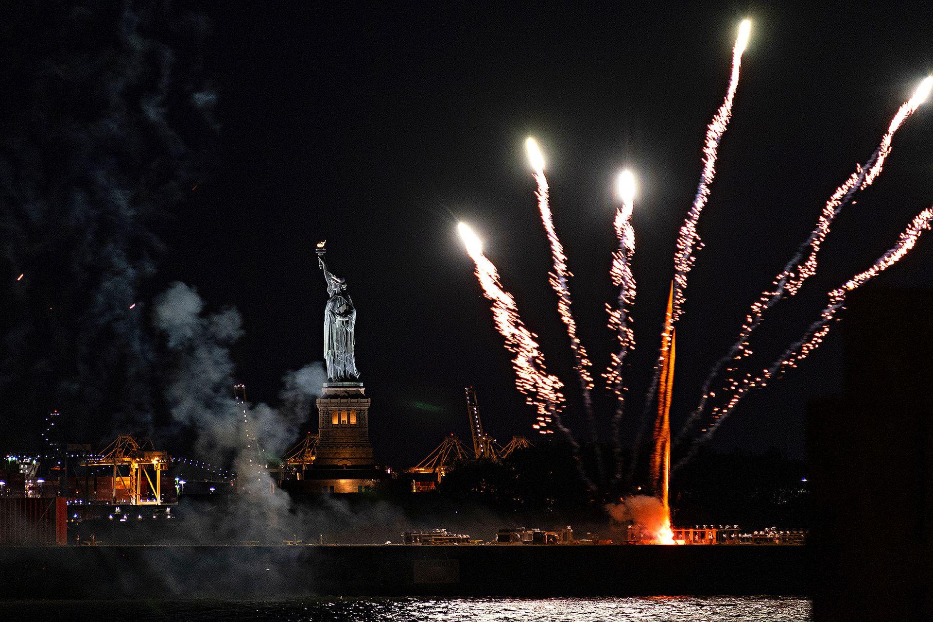 Los fuegos artificiales lanzados desde una barcaza iluminan el puerto de Nueva York y la Estatua de la Libertad