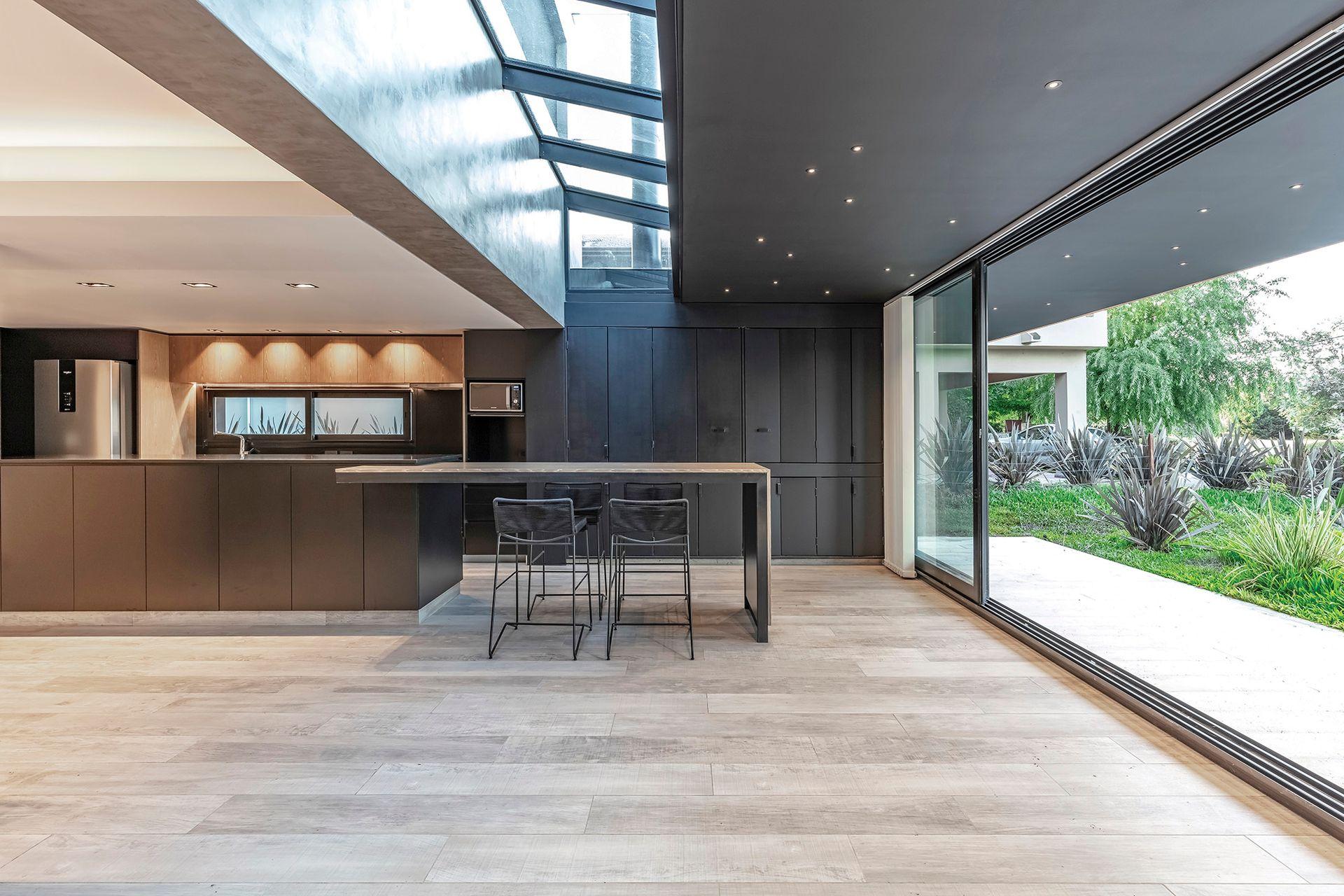 La isla se entendió como el centro neurálgico de la planta baja, donde se cocina y suceden las comidas en familia. Por eso, la pieza es dinámica y tiene un plus de diseño, que combina más de un material.