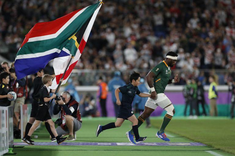 Siya Kolisi entra a jugar la final, con la bandera de Sudáfrica