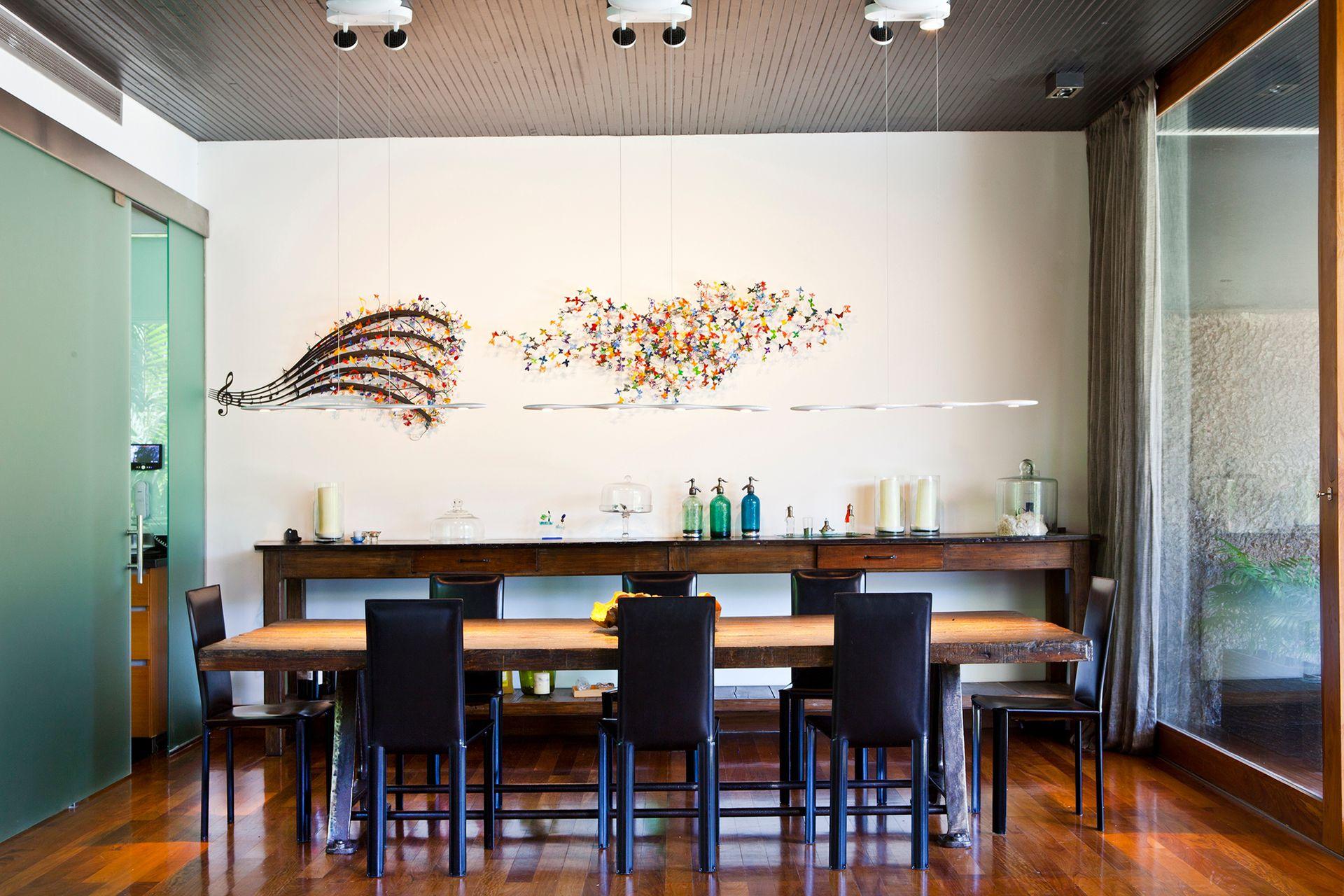 """""""Pentagrama"""" y las mariposas de """"A tu ritmo"""" (Gabriel Soifer), en metal pintado, se explayan sin límites de marcos en la pared, dándole tanto color como volumen."""