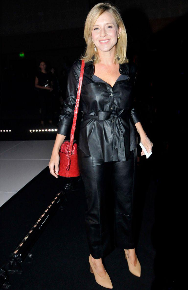 Carla Peterson, con un conjunto total black y un bolso rojo para darle un toque de color a su outfit
