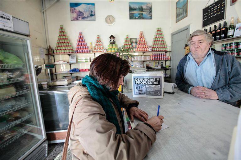 Una vecina rubrica su denuncia en una papeleta que dejará en la urna de la casa de pastas de Jorge Giangreco