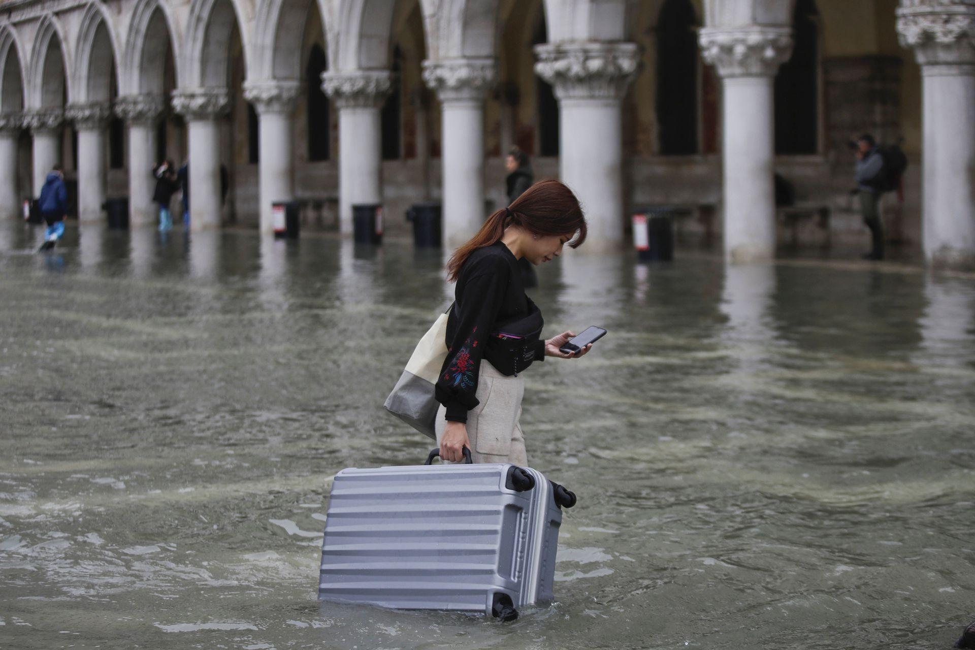 Un turista lleva su equipaje en una plaza inundada de San Marcos, en Venecia