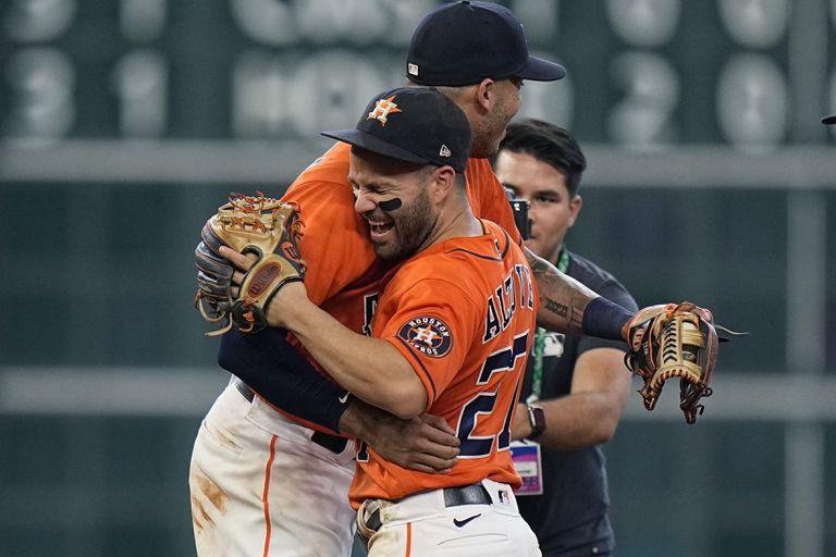 El venezolano José Altuve (derecha) abraza al puertorriqueño Carlos Correa, s compañero de los Astros de Houston, tras la victoria sobre los Medias Blancas de Chicago en el segundo juego de la serie divisional de la Liga Americana, el viernes 8 de octubre de 2021 (AP Foto/David J. Phillip)