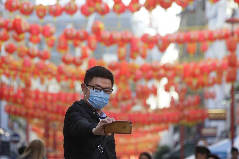 Un turista china se saca una selfie en el barrio chino de Londres con un barbijo