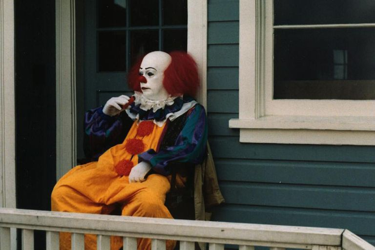 Tim Curry, caracterizado como IT, se está dando aire con un ventilador portátil durante el rodaje