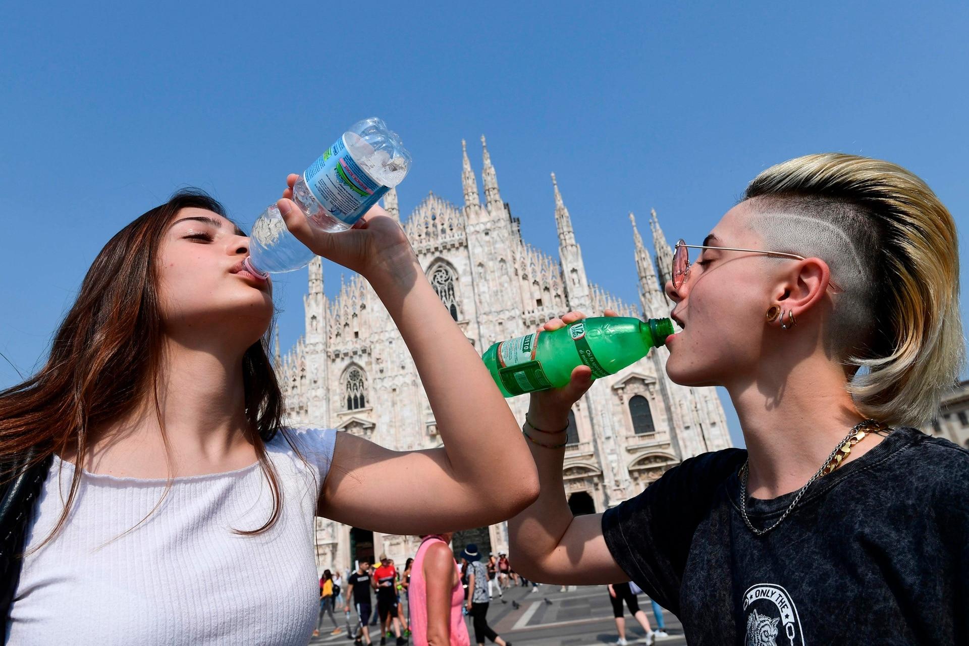 Jóvenes se hidratan frente al Duomo, en Milán, Italia