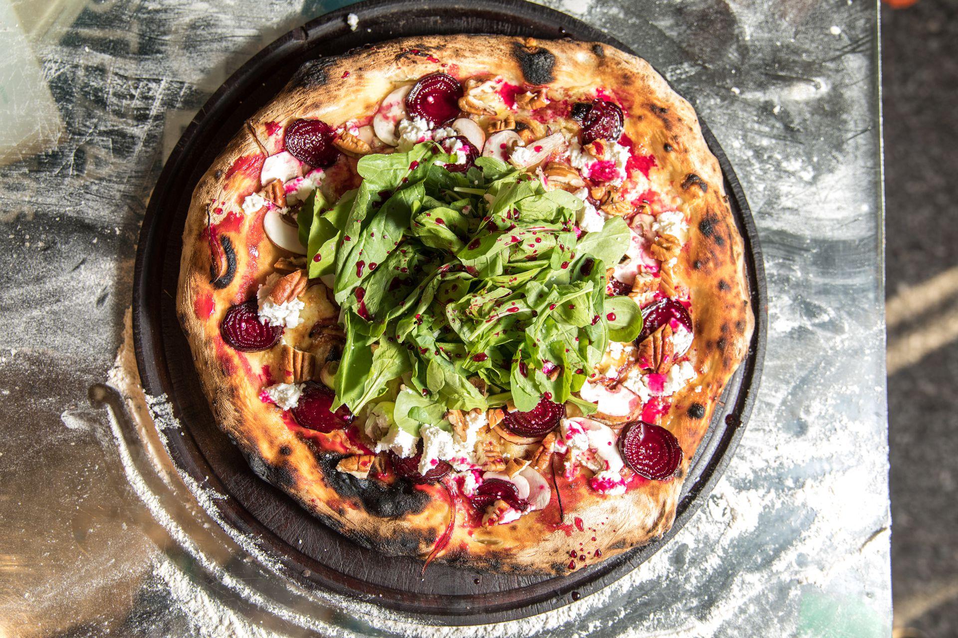 """Pizza """"galáctica"""": remolacha caramelizada, queso de cabra y nuez pecán."""