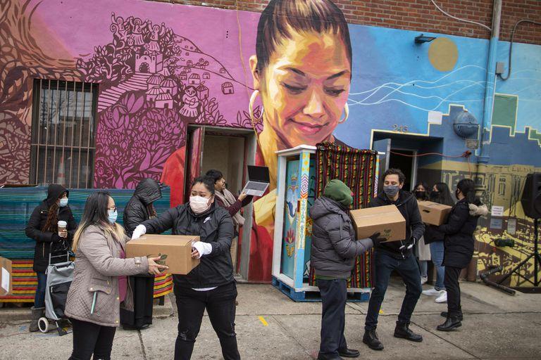 Voluntarios movilizan despensas de alimentos que serán donadas mientras vecinos del barrio reciben información sobre las vacunas contra el Covid en el centro comunitario Mixteca, Brooklyn
