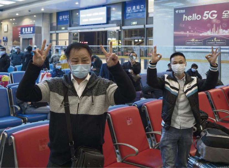 Pasajeros saludan el levantamiento de la cuarentena en la estación central de Wuhan,145x102mm