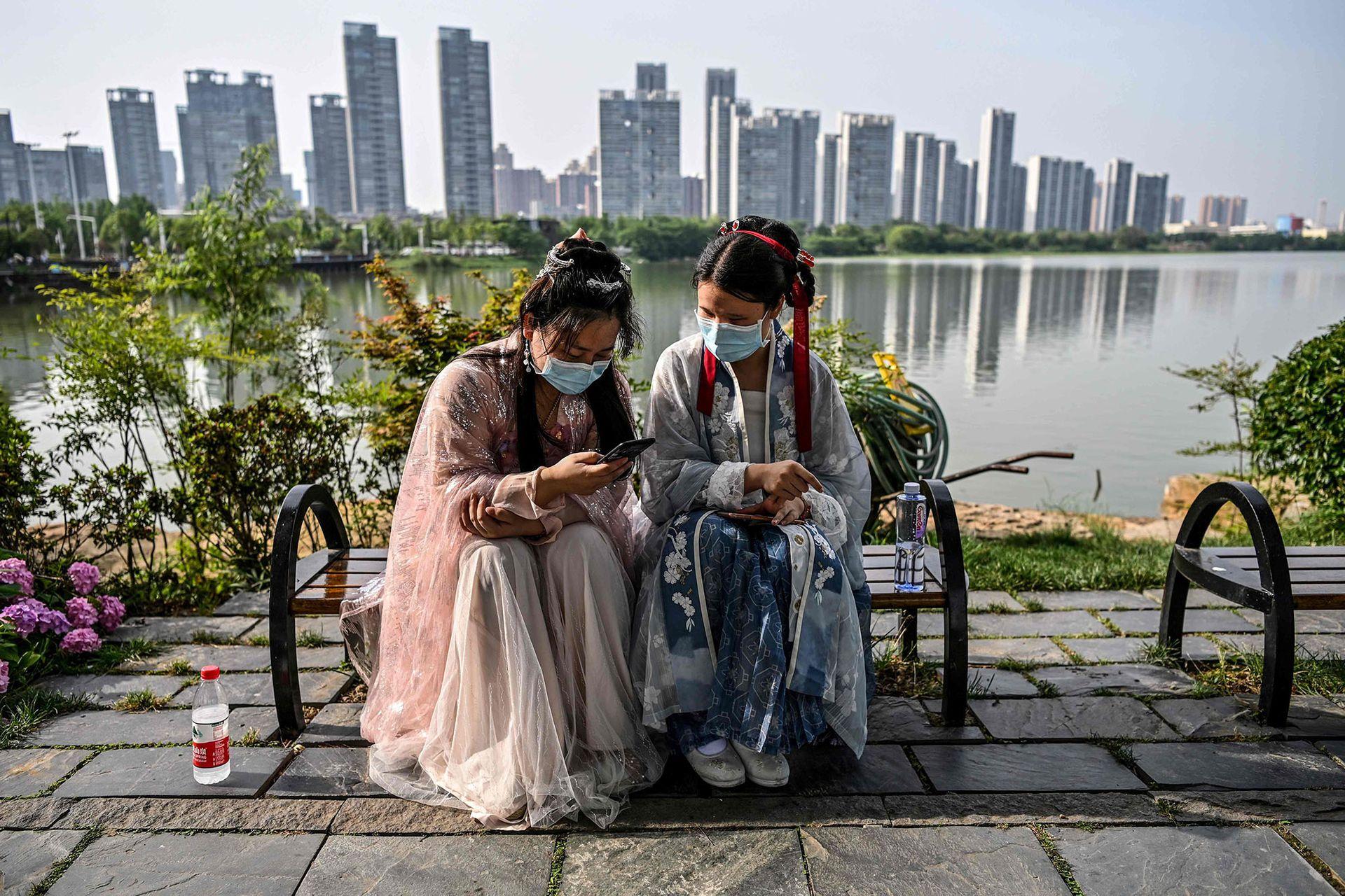 Zona cero pandémica. Dos mujeres conversan junto a un lago al este de Wuhan