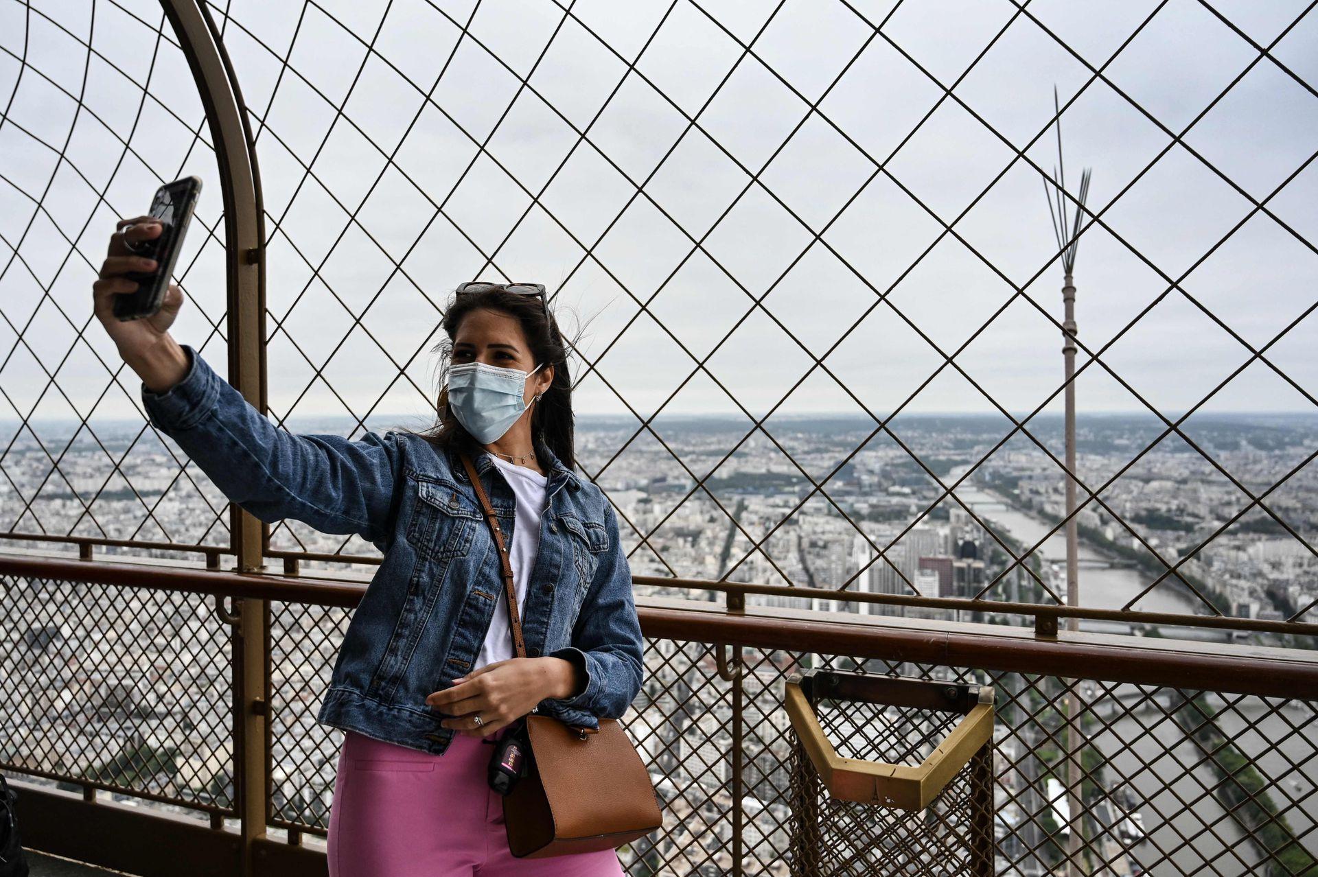 Un visitante se toma una foto mientras visita la Torre Eiffel en París