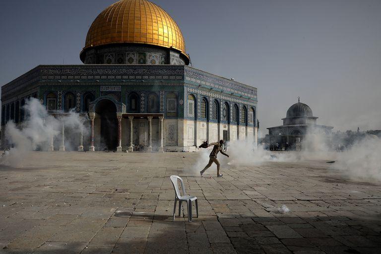 Un manifestante palestino corre entre el gas lacrimógeno lanzado por fuerzas de seguridad israelíes frente a la Cúpula de La Roca en el complejo de la Mezquita de Al-Aqsa, en Jerusalén