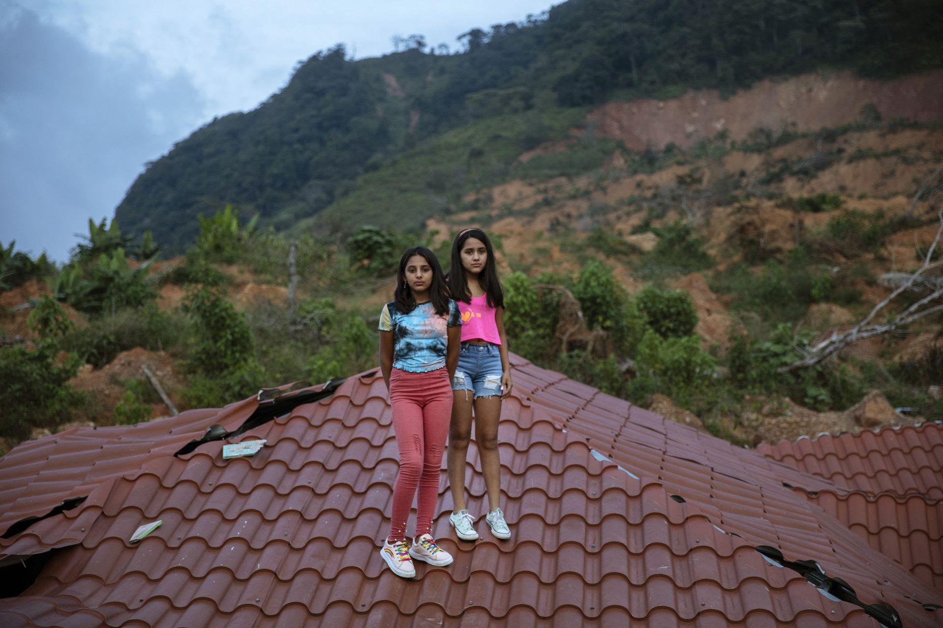 Las gemelas Dulce Alejandra Mejía, y Genesis Mejía, de 12 años, posan sobre el techo de la casa de su vecino devastada por los huracanes en el poblado de La Reina. Sus padres viven en España