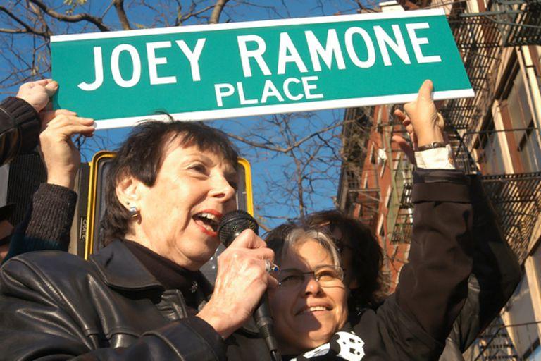"""La madre de Joey Ramone, Charlotte Lesher, sostiene el carte de """"Joey Ramone Place"""" durante la ceremonia en la que se rebautizó la esquina de la 2nd Street & Bowery, en honor a su hijo"""