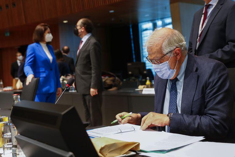 Josep Borrell, derecha, el alto representante de la Unión para Asuntos Exteriores y Política de Seguridad, revisa documentos al tiempo que la política opositora bielorrusa Sviatlana Tsikhanouskaya, izquierda al fondo, dialoga con el ministro chipriota del Exterior, Nicos Christodoulides, durante una reunión de ministros del Exterior de la Unión Europea en Luxemburgo, el lunes 21 de junio de 2021