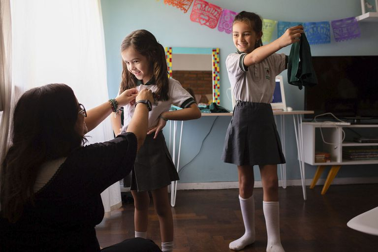 Lola y Violeta intercambian uniformes antes del comienzo de clases; las ayuda Paola, la madre de Violeta
